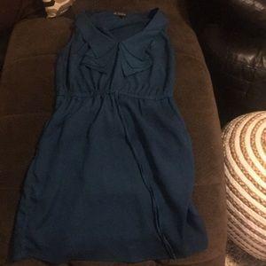 Teal dress with sleek hidden pockets .